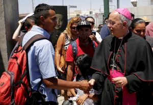 Bishop Mark J. Seitz of El Paso, Texas, greets a Salvadoran migrant June 27, 2019. Bishop Seitz walked and prayed with a group of migrants at the Lerdo International Bridge in El Paso as they sought asylum in the U.S. (CNS photo/Jose Luis Gonzalez, Reuters) See BORDER-BISHOP-BRIDGE June 27, 2019.